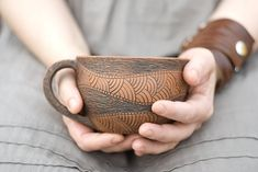 This beautiful mug is decorated with intricate, hand-carved designs.