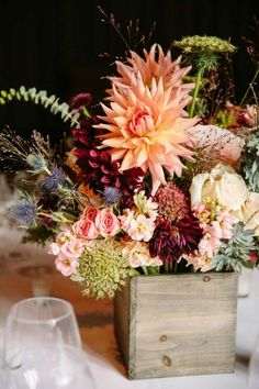 composition florale dans une boîte de bois - roses, chardon bleu, feuilles vertes