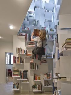 Designer Sallie Trout built shelves in an inaccessible stairwell. She reaches them by using a bosun's chair that is fastened to a chain hoist hanging from the ceiling above.