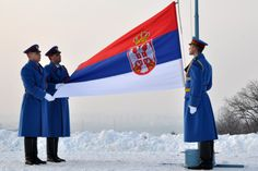 Serbian Army guard of honor in winter uniform raising the national flag of Serbia.