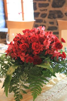 Red roses and red alstromerias with ferns as greenery.   Event by: MJ Weddings & Events