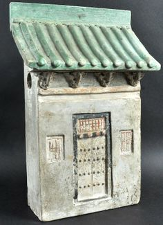 AN UNUSUAL EARLY CHINESE POTTERY MODEL OF A HOUSE possibly Han Dynasty 206 BC–220 AD, with green painted tiled roof. 14. 75ins high.