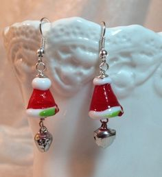 "You'll be ""ringing in the holidays"" with these adorable Santa Hat, with bells, earrings. Handmade Lampwork Glass, these hats are a beautiful red with the white trimmings, a touch of a holly sprig and"