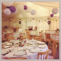 Shades of purple paper lanterns hsnging in marquee adds colour & detail above as we'll as jam jars of flowers on tables.  Www.littleweddinghelper.co.uk