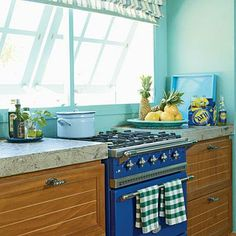 The deep turquoise paint on the walls is a perfect match to the ocean. For a touch of island texture, teak cabinets topped with 3-inch-thick countertops are made from crushed local volcanic rock. The striped Roman shade adds just the right amount of French Country flair. Coastalliving.com
