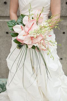 Pink anthurium, white dendrobium orchids, monstera leaves and bear grass. Songs contrasted bold and soft, form and line to create this out of the ordinary bridal bouquet perfect for the bride wanting to add flair to her wedding