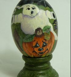 Fun Halloween gourd egg. Hand painted jack-o-lantern, ghost and bat on a gourd the size of a large chicken egg.