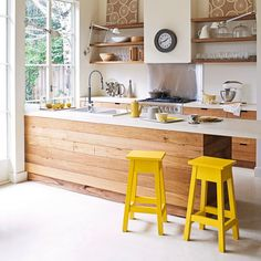 clean and simple with pops of yellow. I'd choose a different accent color but otherwise looovvee this kitchen. Open counter for chatting while prepping!