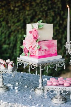 Pretty pink watercolor square tiered wedding cake on silver chandelier cake stand! #pinkweddingcakes