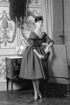 1957 Rose-Marie in a short full-skirted dress with shawl-draped bodice fastened by a large rose just under the décolleté, by Crahay for Nina Ricci, Winter
