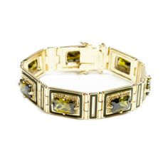 Delicious looking gold tone bracelet, adorned with rectangular shaped olive green stone and secure claspe.