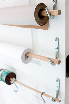 Dowels with rolls of paper and ribbon on the back of a door for wrapping and packaging. Genius!