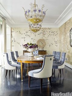 Dining room by Hillary Thomas and Jeff Lincoln features de Gournay wallpaper Plum Blossom, blue and white tufted chairs, and a magnificent chandelier.
