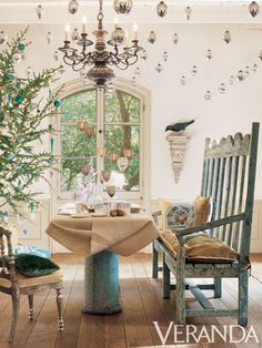 There's something magical about dining under the stars, which this private residence recreated with a constellation of silver ornaments twinkling from the ceiling. The delicate gold-and-white tablesetting complements the subtle patina of the Indian silver chair, antique wooden settle, and rough-hewn floors.  Veranda archives  - Veranda.com