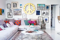 A living room featuring a gray sectional, bright throw pillows, and a unique gallery wall