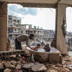 """Una vasca da bagno ancora intatta mentre tutto intorno sono macerie. Un padre che fa il bagno a suoi bimbi. Un sorriso di chi non si meriterebbe di stare lì ed è costretto a farne normalità perché non può andare da nessuna altra parte.  """"L'ora del bagnetto, Gaza 2015"""", è la bellissima foto con cui Emad Nassar ha vinto lo Sharjah Award in Medio Oriente. Questa è Gaza, la Palestina. Non dimentichiamolo."""