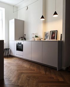 FLOS String Lights by Michael Anastassiades cast a soft glow in this contemporary kitchen with hardwood floors and bright white walls.