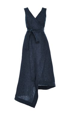 This denim **Alexis** dress features a v-neckline with a wraparound silhouette, a tonal self-belt at the waist, and an asymmetric hem.