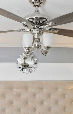 Beautiful ceiling fan. Chrome finish and gray blades with  lights that flip up (as seen here) or down. Available at The Home Depot.