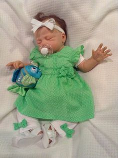 Lillie Beth, reborn baby doll, looks very sporty and cool today in her green seersucker dress with little white knit pants and matching green seersucker bows.