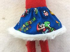 This is a very cute little handmade skirt. The fabric is blue Super Mario World. This fits the 12 inch ELF dolls and measures about 3 inches in length. The pants have an elastic waist that measures about 5 inches but can stretch to about 6 inches. These cute little elves are