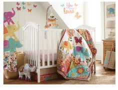 """The Zahara Nursery Collection features globally inspired prints and patterns in a vibrant color-way with accents of a natural shimmering fabric. Whimsical elephants are carried throughout the quilt, diaper stacker and """"mural-like"""" wall decals. The 5 Piece Crib Bedding Set includes a Quilt, 100% Cotton Crib Fitted Sheet, Dust Ruffle, Diaper Stacker and Large Wall Decals to create the perfect """"bohemian"""" look for your nursery."""