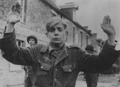 Young German prisoner with his arms raised under the escort of two American soldiers