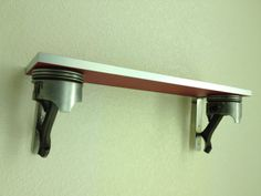 Wall shelf made with two pistons from a small block Chevy. Tig Welded to stainless brackets with four holes to mount the self to the wall and