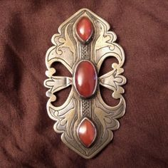 Silver, gilded with fire, cornalines, Turkmenistan     Description     This old (early 20th century) Turkmen belt buckle turned into a pin as a wearable pendant has a lot of charm and is remarkable for the quality and beauty of the carnelians ...      Weight:78,2gr    Height:4,44inch