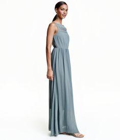 Tåkeblå. En lang, ermeløs kjole i crêpet chiffon med blonde. Kjolen er avskåret i midjen. Gjennombrutt blonde øverst og langs hele ryggen bak. Skjult glidel