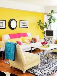 Be bold and choose a primary color that makes a statement, such as this vibrant yellow. Blue and pink accessories bring lively blocks of accent colors, and a classic black-and-white area rug and artwork ensure that color doesn't overwhelm the eye.