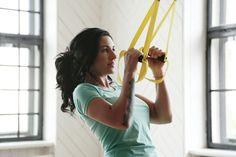 A woman is training with TRX suspension ropes.