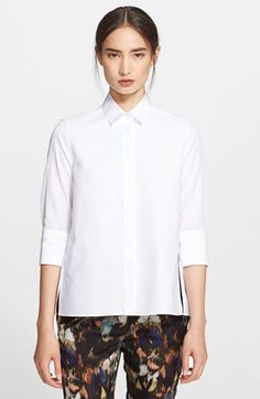 "Free shipping and returns on Valentino Cotton Poplin Blouse at Nordstrom.com. <p><B STYLE=""COLOR:#990000"">Pre-order this style today! Add to Shopping Bag to view approximate ship date. You'll be charged only when your item ships.</b></p><br>A silky box-pleated back panel above a ruffled hem adds soft femininity to a tailored poplin shirt styled with a smart spread collar and three-quarter sleeves. Side slits further ease the modern, boxy silhouette."