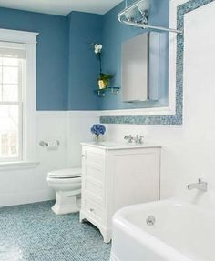 A mosaic tile border and floor echo the steely shade of distant storm clouds in this timeless bath.