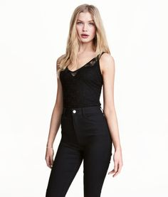 Black. Lace bodysuit with narrow shoulder straps, V-neck, and lined gusset with snap fasteners. Lined at front.