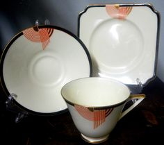Doulton deco: Tango tea trio, V1482, Rd 776716, c1933 (pattern). Red colourway - abstract geometric design with black, red and gold gilt highlights on ivory ground and gold gilt trim.