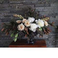 Centerpiece of privet berries, pine boughs, pinecones, roses, peonies, tuberoses, and parrot tulips; Floral design by Honey of a Thousand Flowers