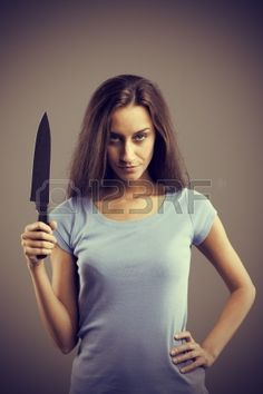 Unsettling dark young woman holding a dengerous knife in his hand