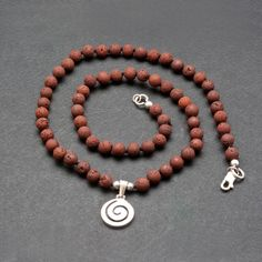 Greek Spiral Sterling Silver Pendant on Natural Brown Lava Beaded Necklace, Minimalist Unisex Statement Necklace, Santorini Lava Jewelry #etsy #brown #birthday #silver #women #round #lobsterclaw #greeknecklace #spiralnecklace #lavanecklace Greek Jewelry, Natural Brown, Santorini, Sterling Silver Pendants, Lava, Spiral, Jewelry Collection, Beaded Necklace, Unisex