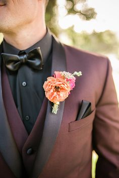 Giracci farms outdoor wedding groom burgundy tuxedo with matching vest and black dress shirt with black faux leather bow tie and bright pink and orange floral boutonniere