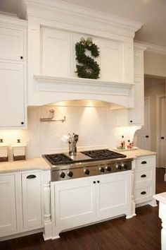 Ornate white cabinetry for range hood matching over head cabinets.