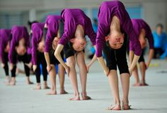 Students stretch during a training session at a gymnastic course at Shenyang Sports School in Shenyang, Liaoning province, on May 9, 2012. Some 60 students, between the ages of 6 to 15, undergo a nine-year gymnastic program that includes foundation courses and gymnastic training courses at Shenyang Sports School. Those who are deemed to be outstanding may be selected to join the national team, according to local media.