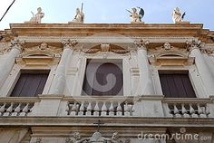 Photo made from Via Daniele Manin to the top of the Monte di Pietà palace in Padua in Veneto (Italy). In the picture you see the upper part of the facade where the entrance door to the east. The photo is entirely occupied by a large balcony with three closed doors punctuated by four white columns. Above the cornice of four statues roof they stand out in the blue sky.