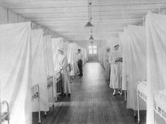 Spanish Flu Epidemic 1918-19. Nurses and orderlies stand by beds separated by sheets to isolate patients in the influenza/pneumonia ward of Walter Reed General Hospital, Washington, D.C.