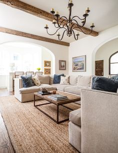 Here's a more contemporary living room design, with white walls, hardwood flooring, and wide arch entries. The white ceiling features the high contrast appearance of rich natural wood exposed beams. Living Room Colors, Rugs In Living Room, Home And Living, Living Room Furniture, Living Room Decor, Modern Living, Natural Living Rooms, Living Room With Beige Couch, Living Room With Sectional