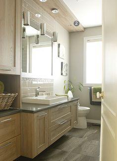 Belle salle de bain claire et spacieuse. A noter : la grande glace qui agrandit l'espace, les dimensions confortables du meuble sous lavabo et des rangements,  les spots encastrés dans une structure faite dans le même matériau que les armoires.