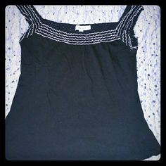 Calvin Klein Sleeveless Shirt Black shirt with woven material around neck and as sleeve; material is black and off-white.  Other material is stretchy and soft.  Beautiful shirt :-) great condition! **see last picture - the top picture shows how the shirt fits around the neck and the bottom picture shows how the shirt fits on the arm ** Calvin Klein Tops Blouses