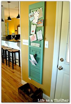 Pretty shutter repurposed as a bulletin board. Whenever you see that someone has thrown out wooden closet doors with slats...stop and pick them up.  They make great room dividers and look good in corners, etc.