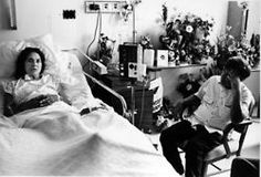 Cesar Chavez visits with Dolores Huerta as she recuperates in hospital after being assaulted by the police. The assault occurred during a protest rally against President H.W. Bush in San Francisco, California. Huerta was beaten with a police baton, resulting in several broken ribs and a destroyed spleen. c. 1988