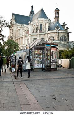 historic Gothic church of Saint Eustache with flying buttresses towers behind newspaper stand on bustling Rue Rambuteau - Stock Image